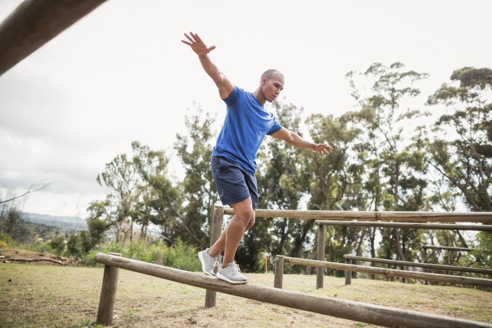 Uomo che cammina in equilibrio sui tronchi