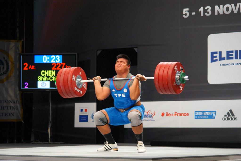 Atleta in accosciata con bilanciere carico mentre esegue clean