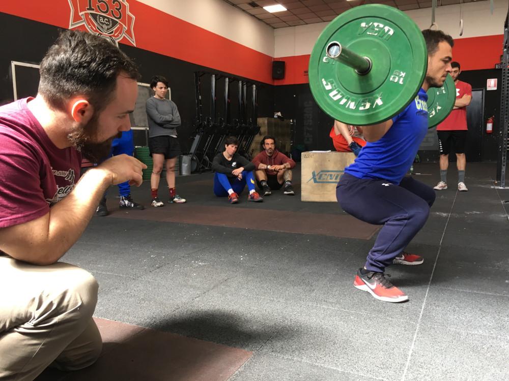 Istruttore che corregge un atleta mentre esegue lo squat
