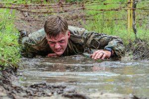 Soldato che striscia nel fango sotto al reticolato di filo spinato