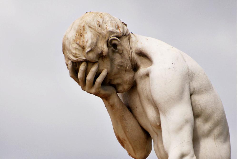 Statua di un uomo con la testa tra le mani