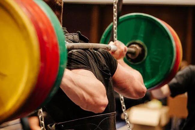 particolare di atleta con un bilanciere sulle spalle