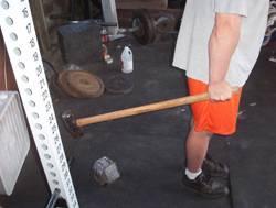 atleta che impugna una mazza per eseguire la weaver stick - posizione finale