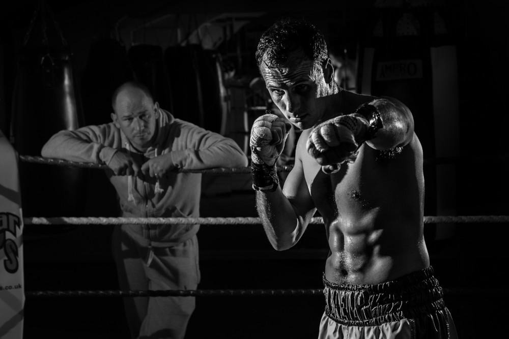 Pugile che si allena sul ring con allenatore che osserva