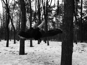 Atleta che esegue il back lever nel bosco